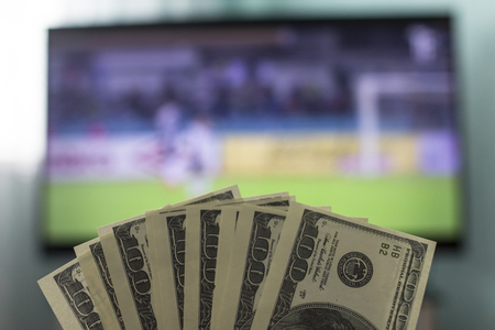 Mens hands keep money dollars against the background of a TV set on which football is playing, close-ups, gain Stock Photo
