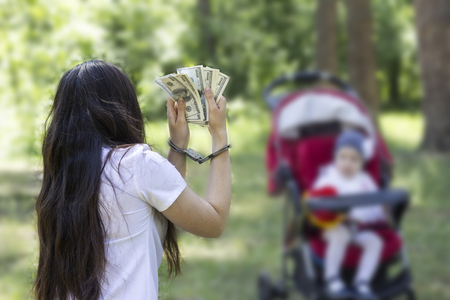 A girl is holding money dollars in handcuffs against the backdrop of a baby in a carriage, arrest, detention for sale by children, trafficking in children, danger