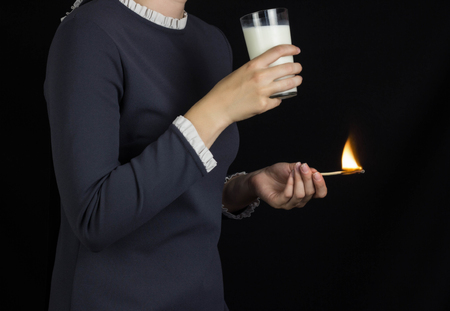 The girl on a black background holds a burning match and drinks milk, burning and pain in the stomach, heartburn and milk, gastritis