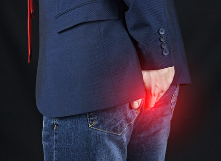 Male businessman holding his ass, hemorrhoids, black background
