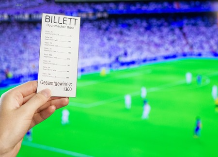 A womans hand holds a bookmakers ticket against the backdrop of a game of football Stock Photo