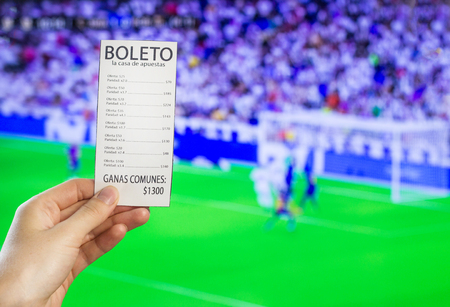 A woman's hand holds a bookmaker's ticket against the backdrop of a game of football