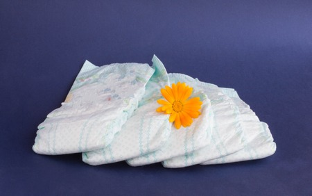 Baby diapers on a blue background and an orange flower on diapers, hygiene