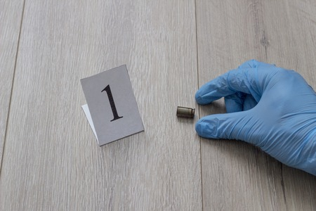 The gloved hand raises the cartridge from the cartridge, the investigation, the evidence, a close-up, cartridge