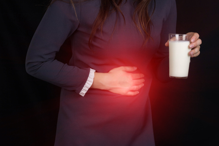 The girl on a black background holds on to her stomach and holds in her hand a glass of milk, heartburn, abdominal pain, close-ups, brash