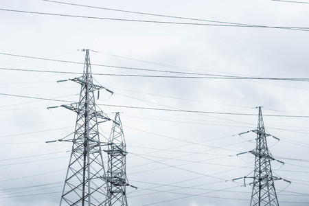 Three electric towers on the sky background, tension, building Stock Photo