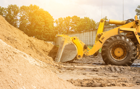 Yellow tractor loader is picking up a bucket of earth, ladle