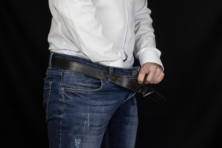 A man in a white shirt and jeans thrust his hand into his pants and holds onto the groin, close-up, black background, adenoma