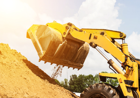 Yellow forklift lifted bucket on a pile with earth, blue sky Stock Photo - 105404735