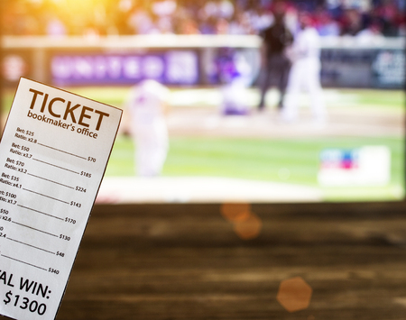 Bookmaker ticket on the background of a TV showing baseball, sports betting, gambler