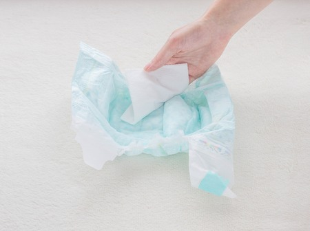 The girl checks the absorbency of a baby nappy with a napkin, close-up, water and diaper