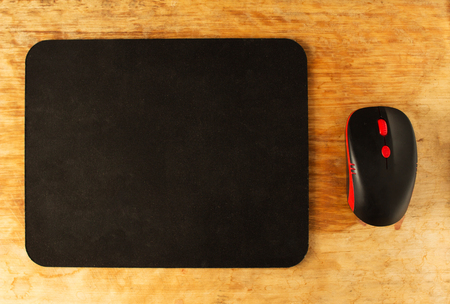 Computer mat and computer mouse on a wooden background, close-up