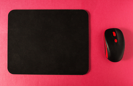 Computer mat and computer mouse on a pink textured background, close-up