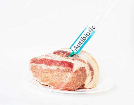 On a white plate a piece of meat pork in which a syringe is injected with an antibiotic, close-up, a white background, chemicals