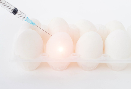 In an egg on a white background, a syringe is injected with a hormone and supplements, a close-up