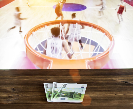 Euro money on a wooden background on the background of a TV on which basketball is shown, euro money and basketball Banco de Imagens