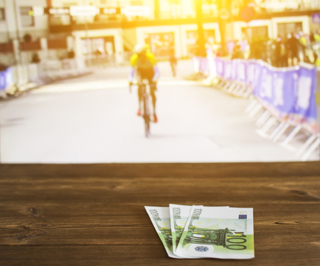 Euro money on the background of a TV on which cycling is shown, sports betting, euro, cycling