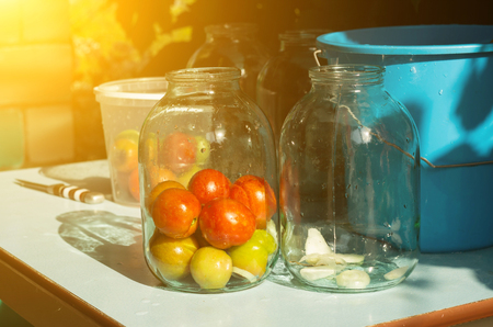 Closure of conservation on the table with tomatoes, sun, outdoor Imagens - 106389542
