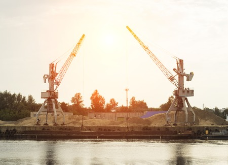 Two port cranes at the riverbank produce river sand, sunset, scow