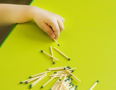 A small child holds a match in the hand on a green background, close-up, danger, fire, child and matches, lucifer match
