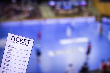 Bookmaker ticket on the background of the TV on which show handball, sports betting, bookmaker