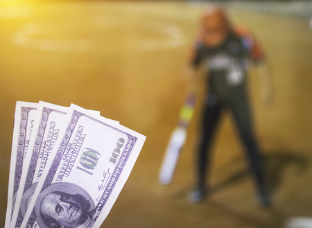 Money dollars on the background of a TV on which show a sports game softball, sports betting, dollars