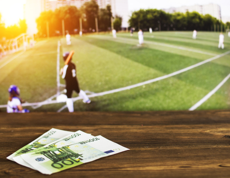 Euro money on the background of the TV on which show the sports game softball, sports betting, softball