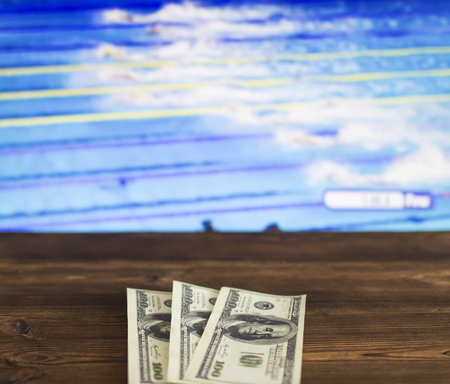 Money dollars on the background of a TV on which show swimming, water sports, sports betting, navigation, dollars