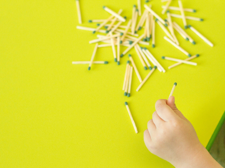 A small child plays with matches, a childs hand takes matches from the table, a close-up, a fire, matches and fire Stock Photo