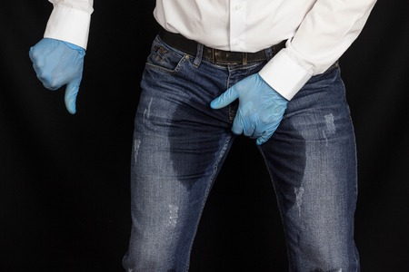 A man in medical gloves and wet pants shows a gesture of shame, prostatitis, incontinence, wet Stock Photo