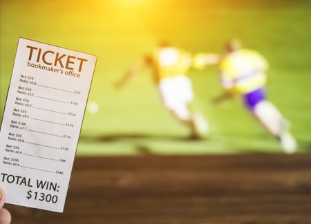 Bookmaker ticket on the background of the TV on which the sport is shown in the game of hurling, sports betting, curling Banco de Imagens