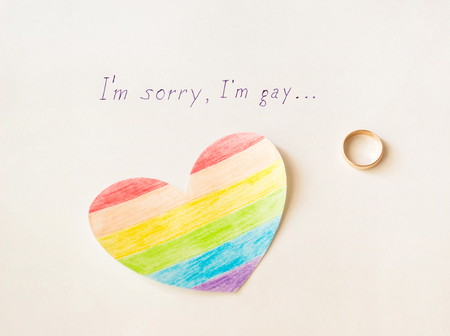 Engagement ring on a white background and an inscription, I'm sorry gay, homosexuality, love Foto de archivo