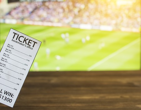Bookmaker ticket on the background of TV on which show Gaelic football, sports betting, Gaelic Football