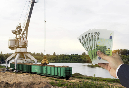 A hand with euro money against a port crane makes loading of wood chips into freight wagons, wood chips and euro