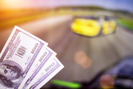 Money dollars on the background of a TV on which show drift on cars, sports betting, drift
