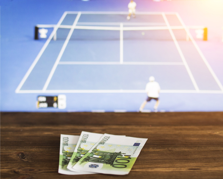 Euro money on the background of the TV on which the game is shown tennis, sports betting, lawn tennis