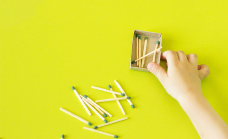 A small child plays with matches, matches matches into boxes, close-ups, fire, matches, play Stock Photo