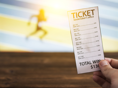 Bookmaker ticket on the background of the TV, which shows athletics, running, jumping, sports betting, bookmaker
