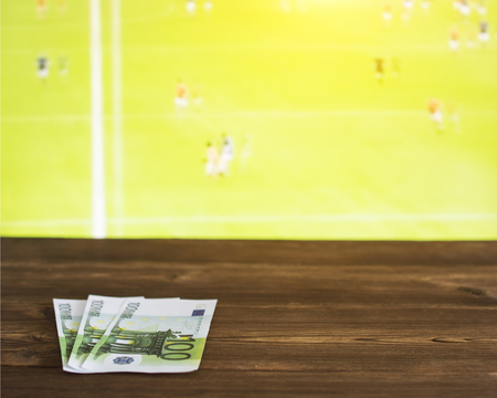 Euro money on the background of the TV on which show Gaelic football, sports betting, Gaelic Football, euro Banco de Imagens