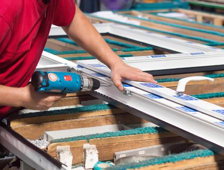 Productie van pvc-ramen, de werknemer wordt met een schroevendraaier met een klik op het pvc-raam geschroefd, close-up, pvc-frame
