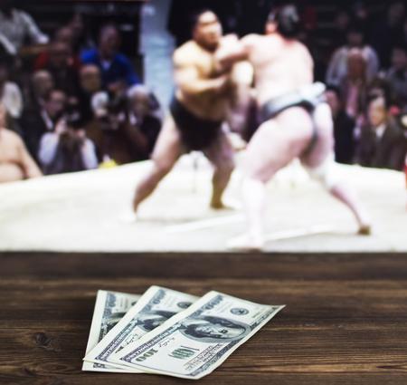 Soldi dollari sullo sfondo di una TV su cui mostrano sport di sumo, scommesse sportive, sumo, dollari