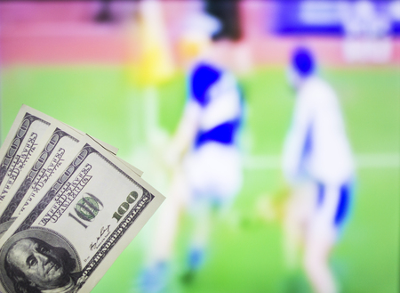 Money dollars on the background of a TV on which the sport is shown in the game of hurling, sports betting, curling Banco de Imagens