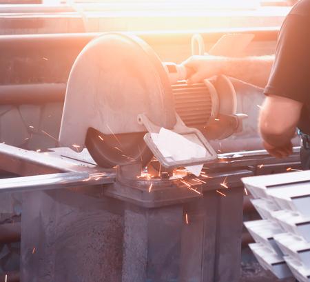 Production of pvc windows, a man cuts a metal profile on a circular saw to make a pvc frame