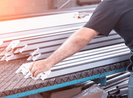 Producción de ventanas de pvc, un hombre quita medidas de un marco de pvc, fabricando ventanas de pvc Foto de archivo