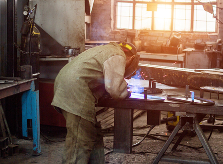 Welder in protective suit at the factory welds parts, workshop, metal