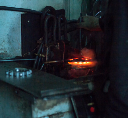 The worker makes hardening heat treatment of the metal gear on a special machine, close-up, hardening of metal