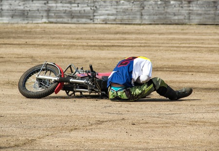 The man fell from a motorcycle and holds on to the abdomen, trauma at a road traffic accident Foto de archivo