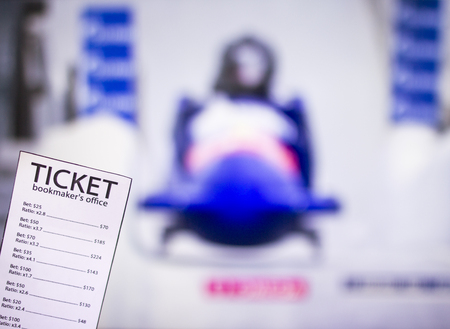 Bookmaker ticket on the background of the TV on which show toboggans, bobsled, sports betting, bookmaker Standard-Bild - 108097698