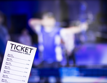 Bookmaker ticket on the background of TV on which show sports archery, sports betting, toxophily