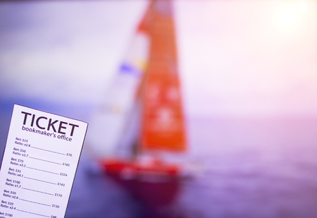 Bookmaker ticket on the background of the TV on which show sailing, sports betting, yachting sport